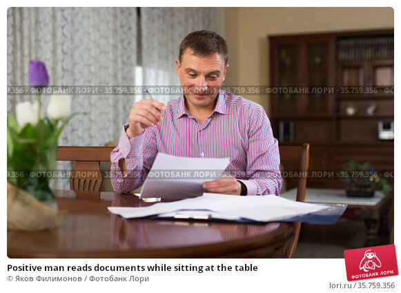 Positive man reads documents while sitting at the table. Стоковое фото, фотограф Яков Филимонов / Фотобанк Лори