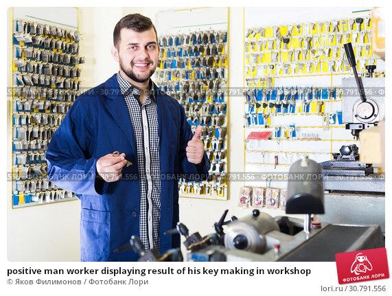 Купить «positive man worker displaying result of his key making in workshop», фото № 30791556, снято 5 апреля 2017 г. (c) Яков Филимонов / Фотобанк Лори