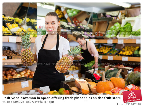 Купить «Positive saleswoman in apron offering fresh pineapples on the fruit store», фото № 30917128, снято 27 апреля 2019 г. (c) Яков Филимонов / Фотобанк Лори