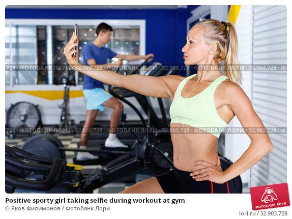 Positive sporty girl taking selfie during workout at gym. Стоковое фото, фотограф Яков Филимонов / Фотобанк Лори
