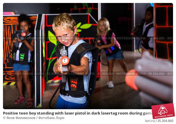 Positive teen boy standing with laser pistol in dark lasertag room during game with friends. Стоковое фото, фотограф Яков Филимонов / Фотобанк Лори
