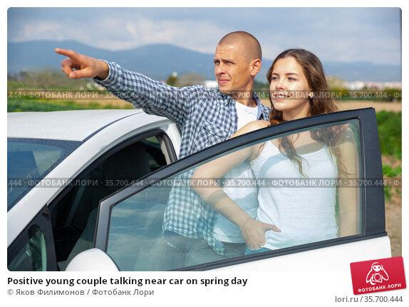 Positive young couple talking near car on spring day. Стоковое фото, фотограф Яков Филимонов / Фотобанк Лори
