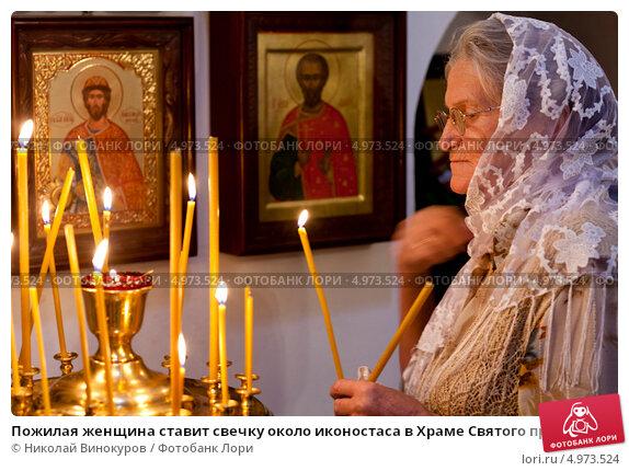 Купить «Пожилая женщина ставит свечку около иконостаса в Храме Святого пророка Божия Илии, что в Китай-городе, в  Ильин день 2 августа 2013», эксклюзивное фото № 4973524, снято 2 августа 2013 г. (c) Николай Винокуров / Фотобанк Лори