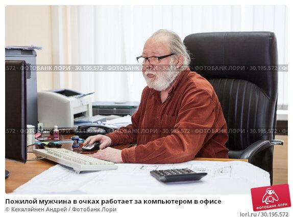 Пожилой мужчина в очках работает за компьютером в офисе (2019 год). Редакционное фото, фотограф Кекяляйнен Андрей / Фотобанк Лори