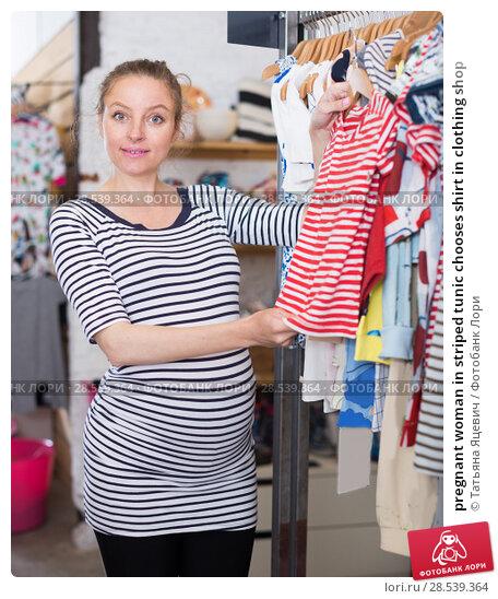 Купить «pregnant woman in striped tunic chooses shirt in clothing shop», фото № 28539364, снято 6 апреля 2017 г. (c) Татьяна Яцевич / Фотобанк Лори