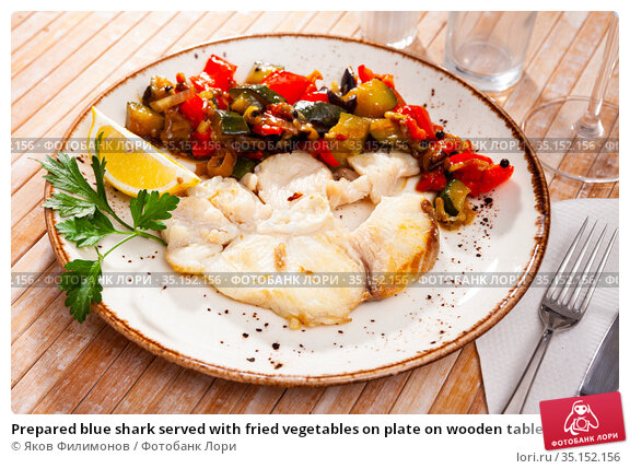 Prepared blue shark served with fried vegetables on plate on wooden table. Стоковое фото, фотограф Яков Филимонов / Фотобанк Лори