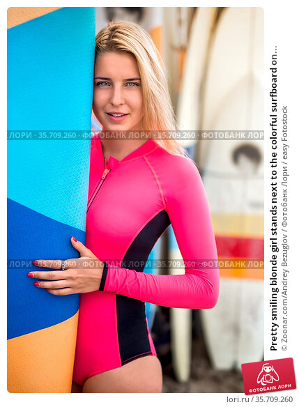 Pretty smiling blonde girl stands next to the colorful surfboard on... Стоковое фото, фотограф Zoonar.com/Andrey Bezuglov / easy Fotostock / Фотобанк Лори