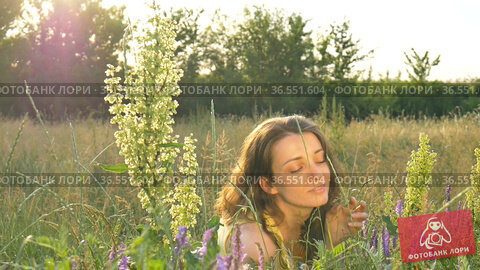 Pretty young girl is sitting in the middle of the field with flowers during summer time, hypersensitivity, asthma, or allergy concept. Стоковое видео, видеограф Ольга Балынская / Фотобанк Лори