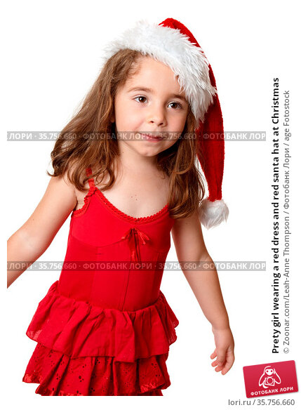 Prety girl wearing a red dress and red santa hat at Christmas. Стоковое фото, фотограф Zoonar.com/Leah-Anne Thompson / age Fotostock / Фотобанк Лори