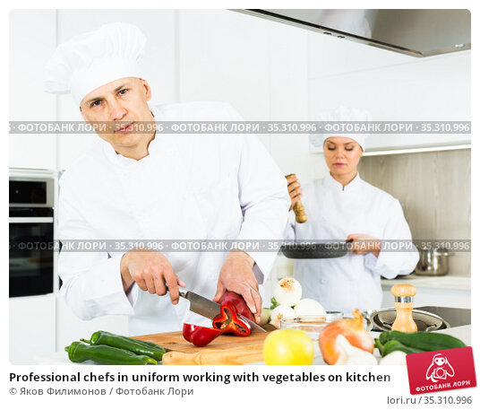 Professional chefs in uniform working with vegetables on kitchen. Стоковое фото, фотограф Яков Филимонов / Фотобанк Лори