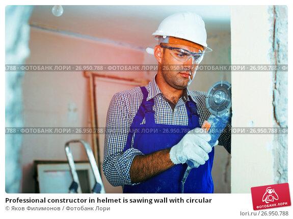 Купить «Professional constructor in helmet is sawing wall with circular», фото № 26950788, снято 18 мая 2017 г. (c) Яков Филимонов / Фотобанк Лори