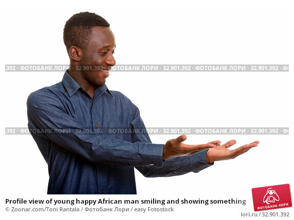 Profile view of young happy African man smiling and showing something. Стоковое фото, фотограф Zoonar.com/Toni Rantala / easy Fotostock / Фотобанк Лори