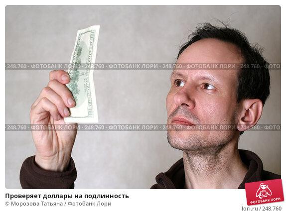 Купить «Проверяет доллары на подлинность», фото № 248760, снято 9 апреля 2008 г. (c) Морозова Татьяна / Фотобанк Лори
