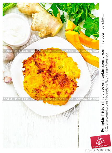 Pumpkin fritters in a plate on napkin, sour cream in a bowl, parsley... Стоковое фото, фотограф Zoonar.com/kostrez / easy Fotostock / Фотобанк Лори