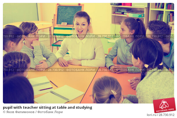 Купить «pupil with teacher sitting at table and studying», фото № 28730912, снято 28 января 2018 г. (c) Яков Филимонов / Фотобанк Лори