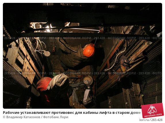 Рабочие устанавливают противовес для кабины лифта в старом доме, фото № 283428, снято 21 марта 2008 г. (c) Владимир Катасонов / Фотобанк Лори