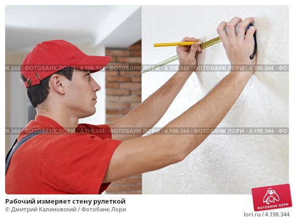 Купить «Рабочий измеряет стену рулеткой», фото № 4198344, снято 2 декабря 2012 г. (c) Дмитрий Калиновский / Фотобанк Лори