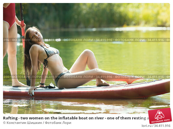 Rafting - two women on the inflatable boat on river - one of them resting and another rowing with an oar. Стоковое фото, фотограф Константин Шишкин / Фотобанк Лори