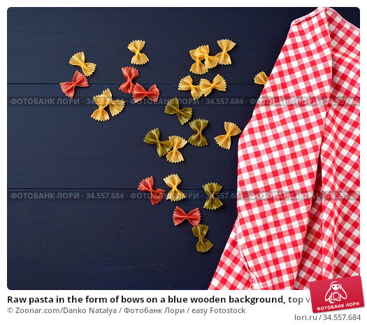 Raw pasta in the form of bows on a blue wooden background, top view... Стоковое фото, фотограф Zoonar.com/Danko Natalya / easy Fotostock / Фотобанк Лори