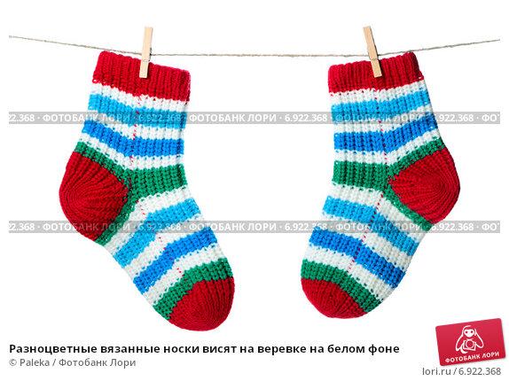 Купить «Разноцветные вязанные носки висят на веревке на белом фоне», фото № 6922368, снято 3 декабря 2014 г. (c) Paleka / Фотобанк Лори