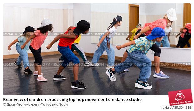 Rear view of children practicing hip hop movements in dance studio. Стоковое фото, фотограф Яков Филимонов / Фотобанк Лори