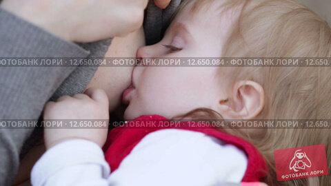 Купить «Ребенка кормят грудью», видеоролик № 12650084, снято 26 апреля 2014 г. (c) Потийко Сергей / Фотобанк Лори