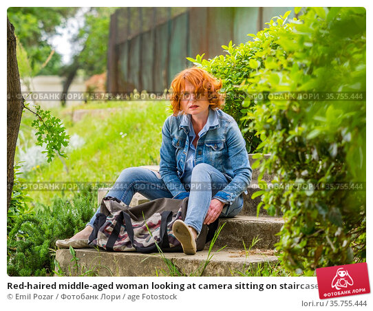 Red-haired middle-aged woman looking at camera sitting on staircase... Стоковое фото, фотограф Emil Pozar / age Fotostock / Фотобанк Лори
