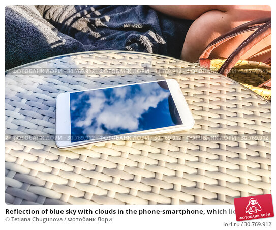 Купить «Reflection of blue sky with clouds in the phone-smartphone, which lies on a bright wicker table against the background. Blur and abstraction.», фото № 30769912, снято 6 августа 2018 г. (c) Tetiana Chugunova / Фотобанк Лори