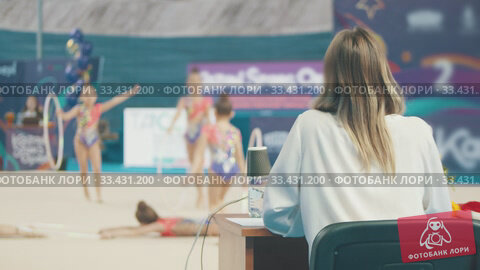Купить «Rhythmic gymnastics tournament - woman judge watching the performance and giving it an assessment», видеоролик № 33431200, снято 26 марта 2020 г. (c) Константин Шишкин / Фотобанк Лори
