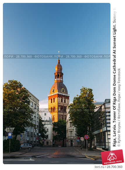 Купить «Riga, Latvia. Tower Of Riga Dom Dome Cathedral At Sunset Light. Sunny Blue Sky Background. Belfry Bell Tower In Golden Hour At Sunset Or Sunrise Time.», фото № 28700360, снято 1 июля 2016 г. (c) easy Fotostock / Фотобанк Лори