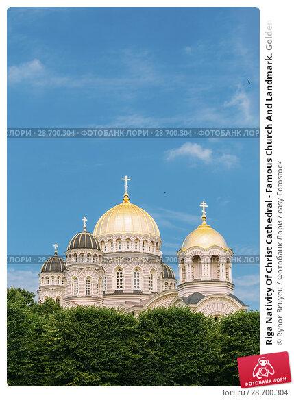 Купить «Riga Nativity Of Christ Cathedral - Famous Church And Landmark. Golden Yellow Domes On Blue Sunny Sky Background At Summer Season.», фото № 28700304, снято 1 июля 2016 г. (c) easy Fotostock / Фотобанк Лори