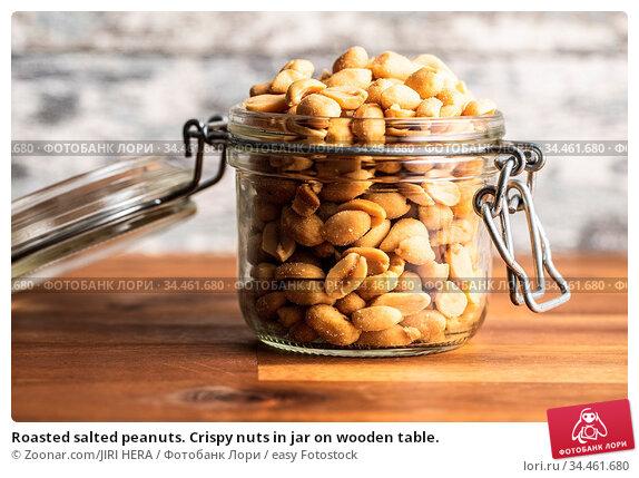Roasted salted peanuts. Crispy nuts in jar on wooden table. Стоковое фото, фотограф Zoonar.com/JIRI HERA / easy Fotostock / Фотобанк Лори