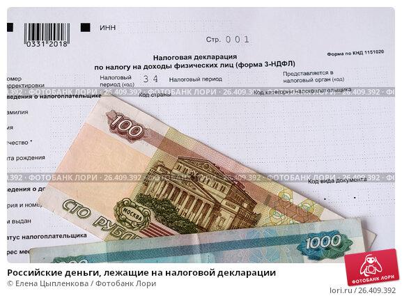 Купить «Российские деньги, лежащие на налоговой декларации», фото № 26409392, снято 8 мая 2017 г. (c) Елена Цыпленкова / Фотобанк Лори