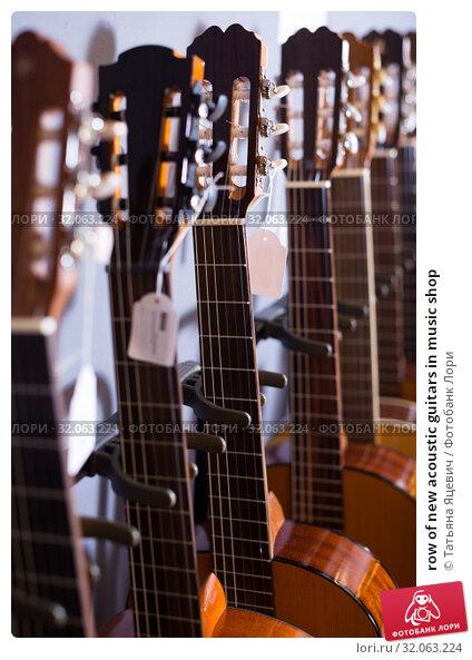 row of new acoustic guitars in music shop. Стоковое фото, фотограф Татьяна Яцевич / Фотобанк Лори