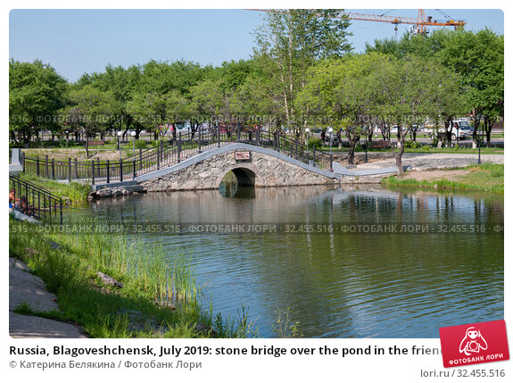 Russia, Blagoveshchensk, July 2019: stone bridge over the pond in the friendship Park in the city of Blagoveshchensk in the summer. Стоковое фото, фотограф Катерина Белякина / Фотобанк Лори