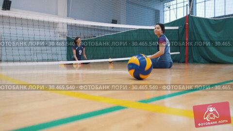 RUSSIA, KAZAN. 09-02-2019: Sports for disabled people. Rolling the ball to a young women sitting on the floor. Редакционное видео, видеограф Константин Шишкин / Фотобанк Лори