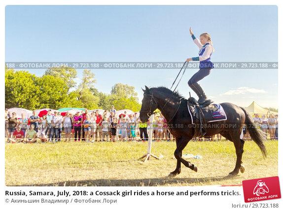 Купить «Russia, Samara, July, 2018: a Cossack girl rides a horse and performs tricks.», фото № 29723188, снято 29 июля 2018 г. (c) Акиньшин Владимир / Фотобанк Лори