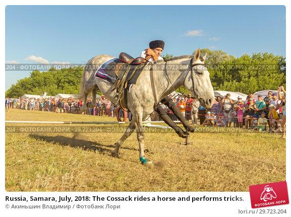 Купить «Russia, Samara, July, 2018: The Cossack rides a horse and performs tricks.», фото № 29723204, снято 29 июля 2018 г. (c) Акиньшин Владимир / Фотобанк Лори
