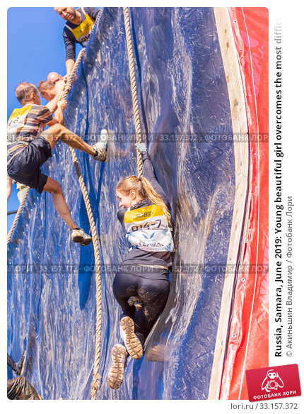 Купить «Russia, Samara, June 2019: Young beautiful girl overcomes the most difficult obstacle in the race of heroes of Everest with the help of a rope», фото № 33157372, снято 8 июня 2019 г. (c) Акиньшин Владимир / Фотобанк Лори