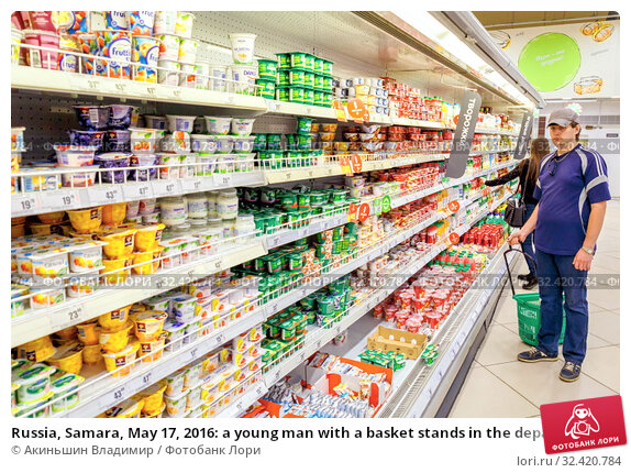 Купить «Russia, Samara, May 17, 2016: a young man with a basket stands in the department of dairy products in a large supermarket .», фото № 32420784, снято 17 мая 2016 г. (c) Акиньшин Владимир / Фотобанк Лори