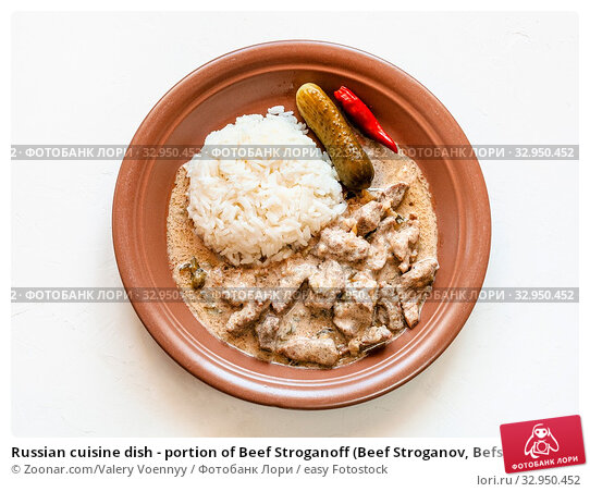 Russian cuisine dish - portion of Beef Stroganoff (Beef Stroganov, Befstroganov) pieces of stewed meat in sour cream with boiled rice on brown plate on white board. Стоковое фото, фотограф Zoonar.com/Valery Voennyy / easy Fotostock / Фотобанк Лори