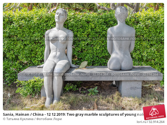 Sania, Hainan / China - 12 12 2019: Two gray marble sculptures of young naked women on a garden bench in summer. Редакционное фото, фотограф Татьяна Куклина / Фотобанк Лори