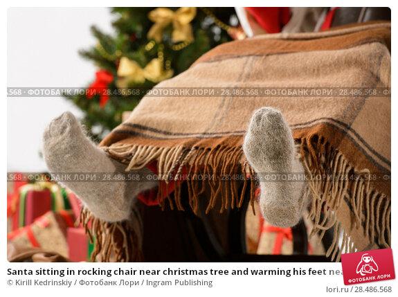 Купить «Santa sitting in rocking chair near christmas tree and warming his feet near fireplace. Closeup of Santa's feet in wool socks», фото № 28486568, снято 19 января 2013 г. (c) Ingram Publishing / Фотобанк Лори