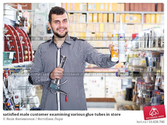satisfied male customer examining various glue tubes in store. Стоковое фото, фотограф Яков Филимонов / Фотобанк Лори