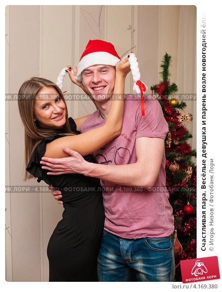 Купить «Счастливая пара. Весёлые девушка и парень возле новогодней ёлки в колпаке Санта Клауса», эксклюзивное фото № 4169380, снято 5 января 2013 г. (c) Игорь Низов / Фотобанк Лори
