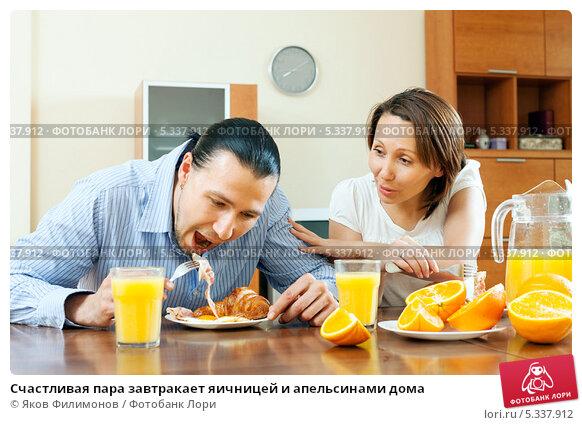 Купить «Счастливая пара завтракает яичницей и апельсинами дома», фото № 5337912, снято 17 мая 2013 г. (c) Яков Филимонов / Фотобанк Лори