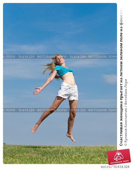 Счастливая женщина прыгает на летнем зеленом поле на фоне голубого неба. Стоковое фото, фотограф Куликов Константин / Фотобанк Лори