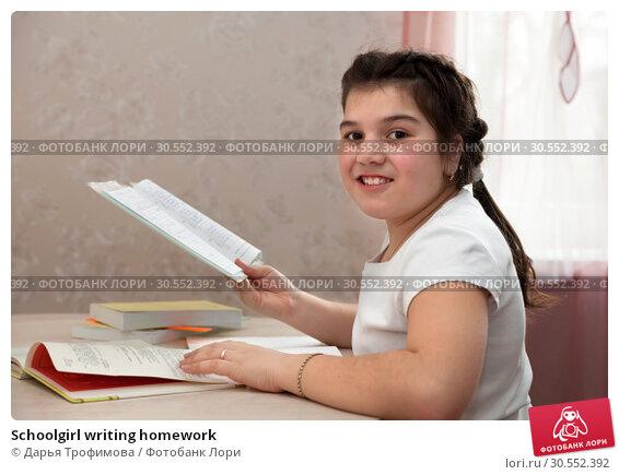 Купить «Schoolgirl writing homework», фото № 30552392, снято 29 марта 2015 г. (c) Дарья Филимонова / Фотобанк Лори
