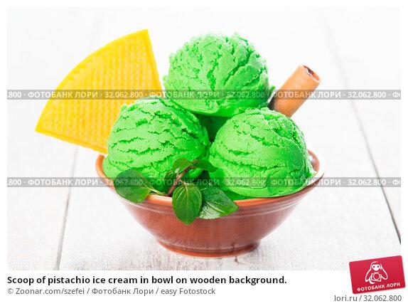 Scoop of pistachio ice cream in bowl on wooden background. Стоковое фото, фотограф Zoonar.com/szefei / easy Fotostock / Фотобанк Лори