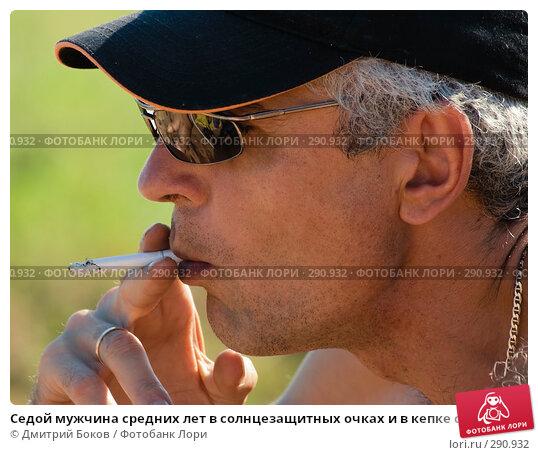 Седой мужчина средних лет в солнцезащитных очках и в кепке с удовольствием курит сигарету, фото № 290932, снято 15 июля 2006 г. (c) Дмитрий Боков / Фотобанк Лори
